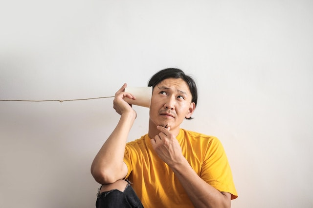 Guy sitting down with a string phone on left ear