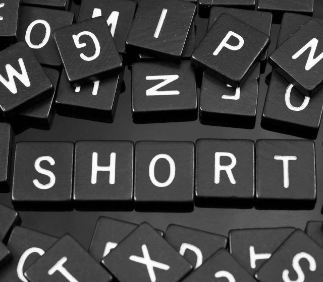 "Black scramble tiles spelling the word ""short"""