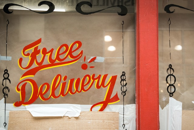 Free delivery painted on a shop window