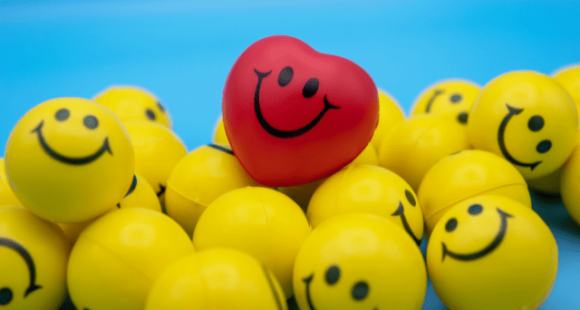 Heart-Shaped Stress Ball in Pile of Smiley-Faced Stress Balls