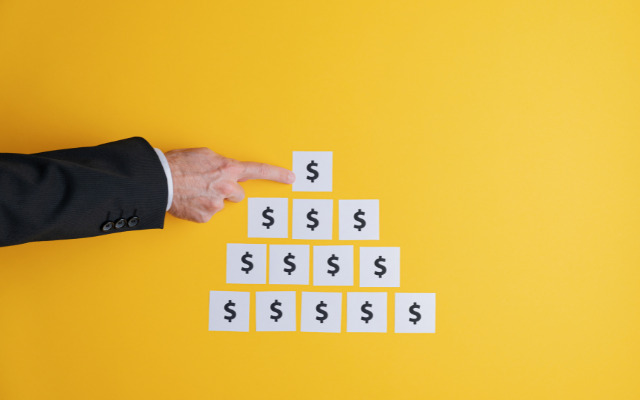Man pointing to a post it pyramid with dollar sign
