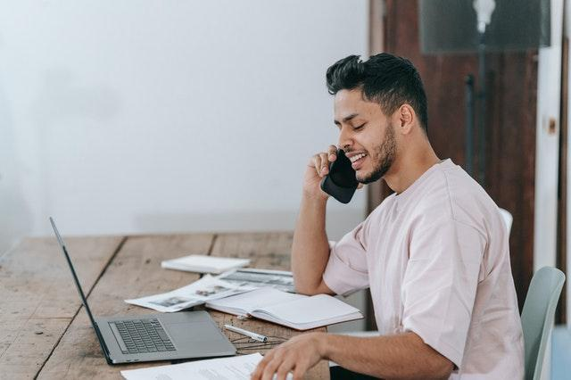 Man With Laptop Talking on Phone