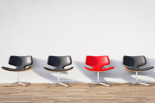 Red Office Chair in Row of Black Office Chairs
