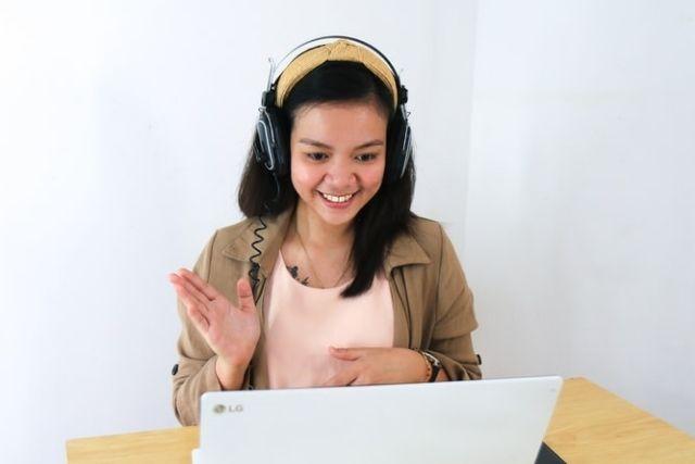 Woman Speaking to Laptop Webcam